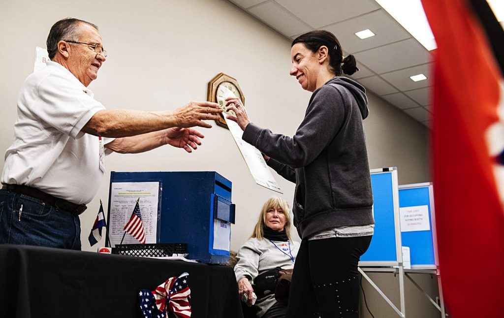 Pitkin County election official John Ortega, left, assists Jennifer Ryan as she drops her ballot for the presidential primaries on Super Tuesday, March 3, 2020. (Kelsey Brunner/The Aspen Times)