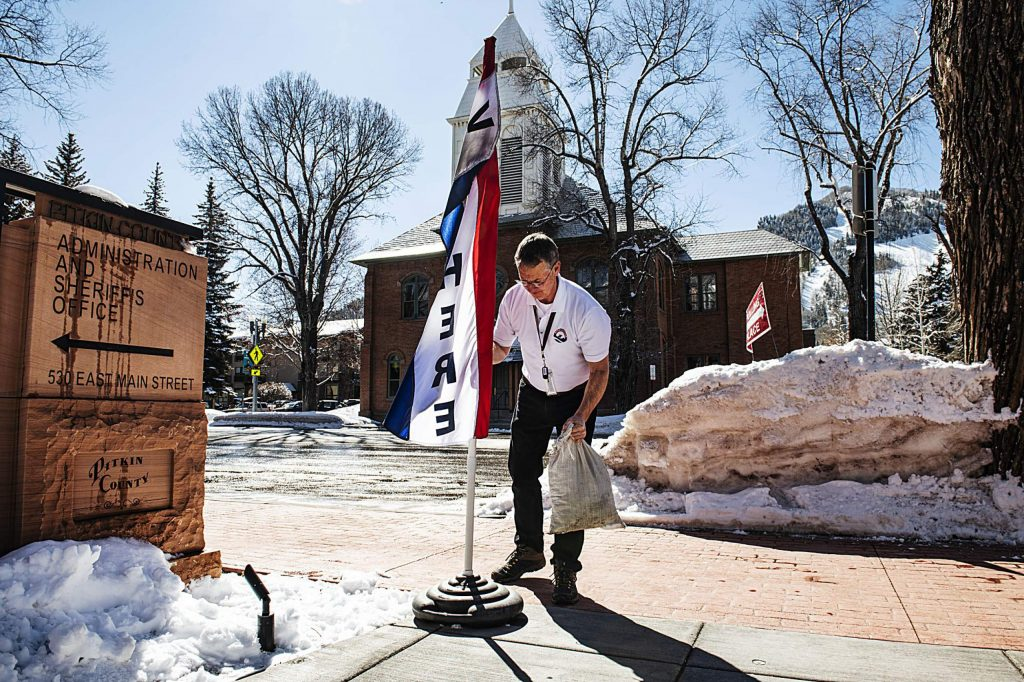 "Pitkin County election specialist adjusts the ""Vote Here"" flag outside of the Pitkin County government building to encourage voters to cast their ballot on Super Tuesday, March 3, 2020. (Kelsey Brunner/The Aspen Times)"