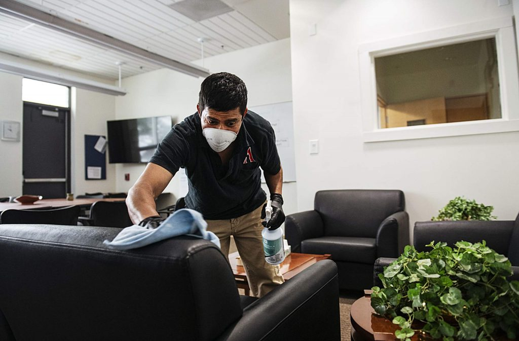 Jose Solís wipes down a chair in the superintendent's office in Aspen High School on Thursday, March 19, 2020. The crew will be finished disinfecting the school on Friday and are asking that no one enters any building on campus to keep it clean. (Kelsey Brunner/The Aspen Times)