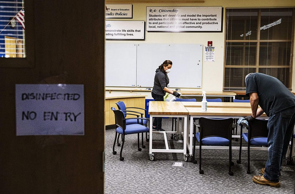 Maria Peña, left, and Wilibaldo Briceno disinfect a board room in the front of Aspen High School on Thursday, March 19, 2020. (Kelsey Brunner/The Aspen Times)