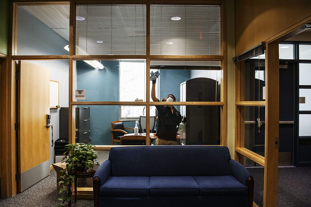 Jose Solís wipes the windows with disinfecting spray in an administrative office at the entrance of Aspen High School on Thursday, March 19, 2020. (Kelsey Brunner/The Aspen Times)