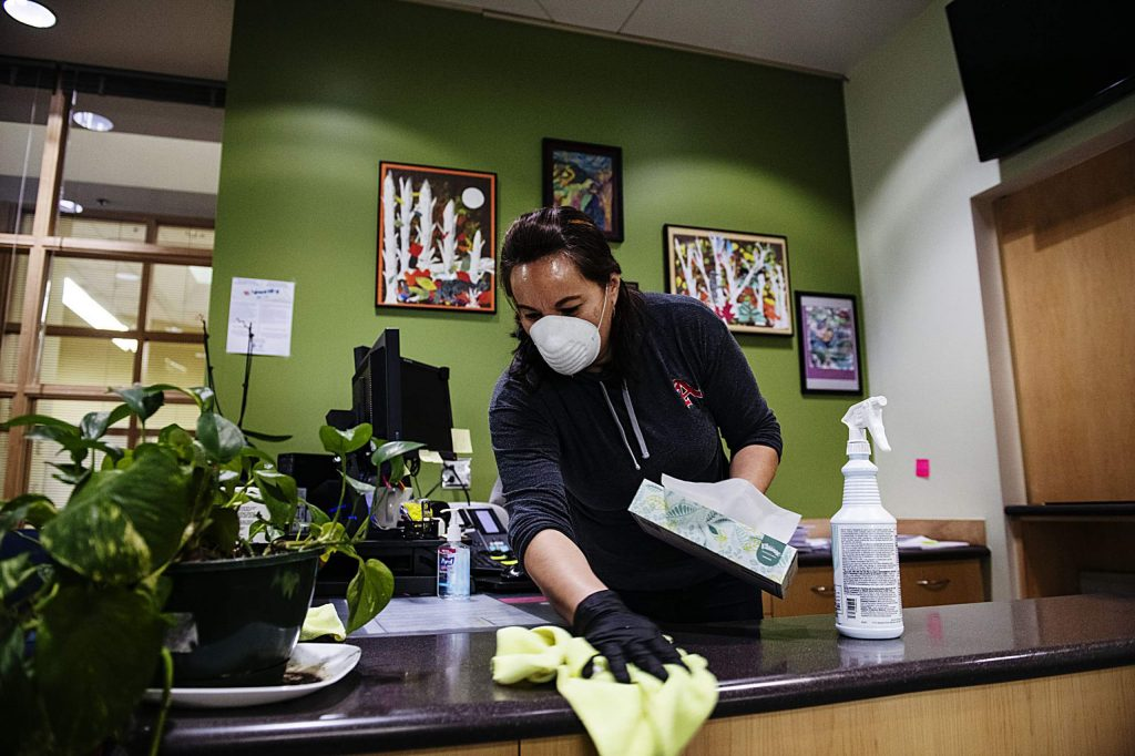 Maria Peña wipes down a desk with disinfectant spray in the administrative offices at Aspen High School on Thursday, March 19, 2020. (Kelsey Brunner/The Aspen Times)