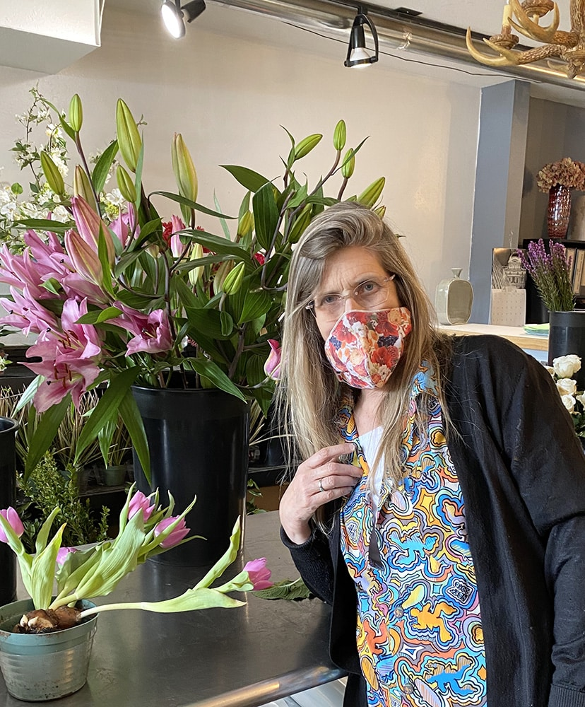 Beth Gill of the Aspen Branch Design wears a mask in her flower shop made by a vendor. Something Different Linens sent her a stash of masks they made, which she's giving away while supplies last.