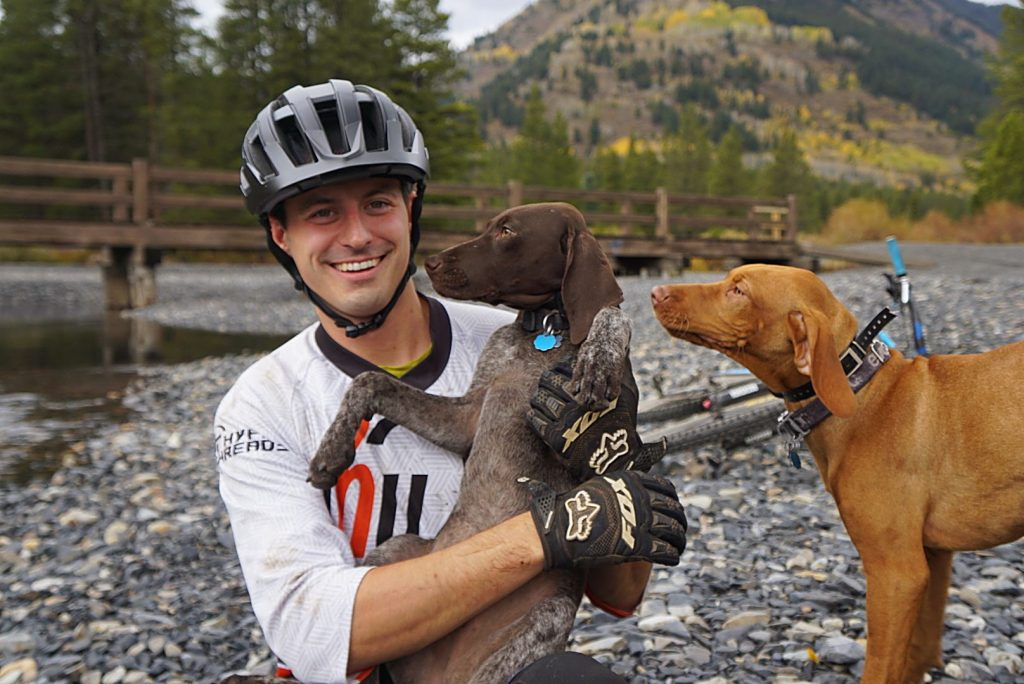 Adam Miller takes a break during a bike ride in Crested Butte with his dogs.