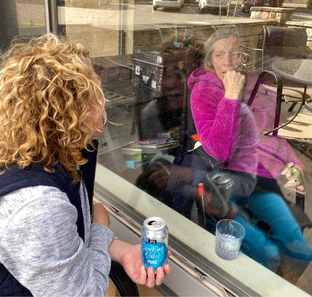 Heather Bryan visits with her mother, Judy Mackay, through a window at Heritage Park Care Center in Carbondale. Bryan has created special