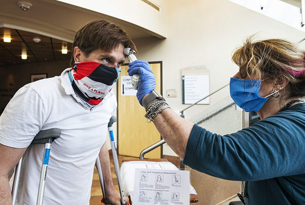 Aspen Valley Hospital's Debra Demeulenaere takes the temperature of patient Jamie Grenney before he enters through the east entrance of the hospital on Tuesday, April 14, 2020. (Kelsey Brunner/The Aspen Times)