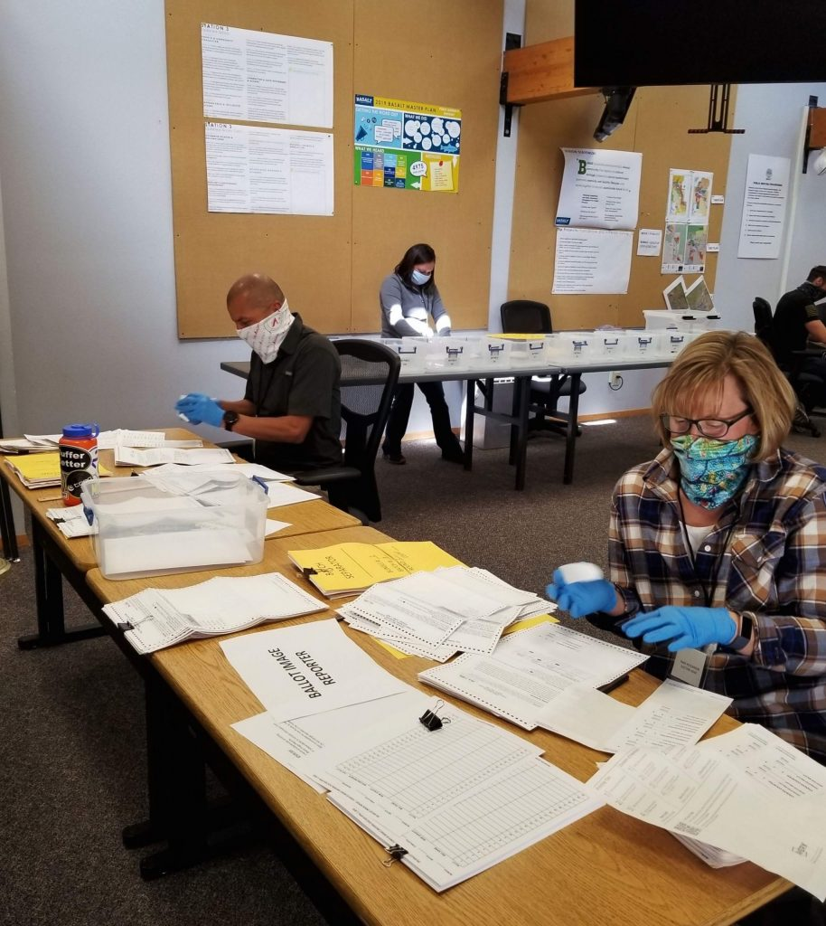 Volunteer election judges for the town of Basalt prepare to process ballots on Tuesday. They wore masks and gloves because of the coronavirus threat.