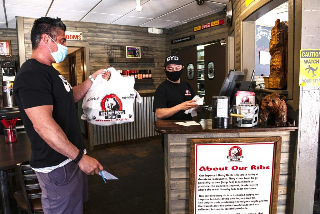 Hickory House's Henry Pineda gives a take-out customer his receipt in Aspen on Wednesday, April 22, 2020. (Kelsey Brunner/The Aspen Times)