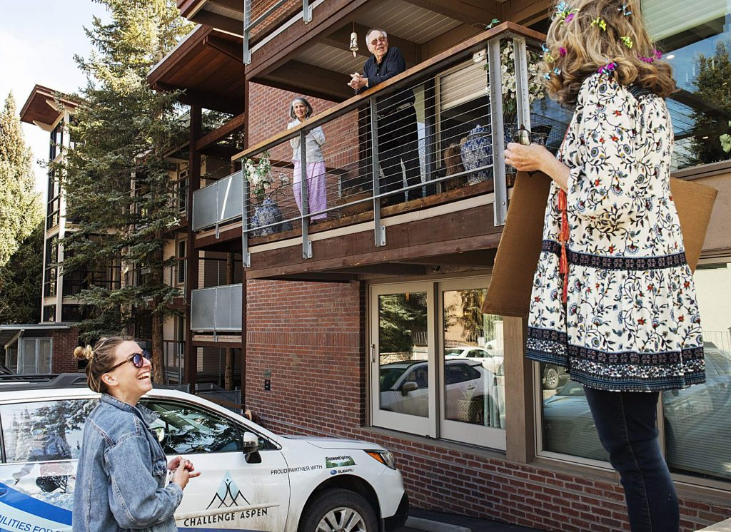 Challenge Aspen program coordinator Callie Dickson, left, and program director Deb Sullivan, right, talk to participant Jen Arkin, center left, and her stepdad Bernie Weiss from their balcony during a now reoccurring Wednesday drive by in Aspen on Wednesday, April 1, 2020. The duo also delivered a bingo card to play over zoom with other Challenge Aspen participants. (Kelsey Brunner/The Aspen Times)