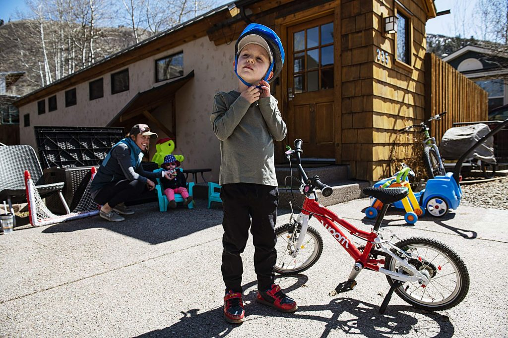 Cooper Gellert, 4, buckles his bike helmet as his mom, Lacey Gellert, left, and little sister, Sloane Gellert, 1, take a snack break in the shade outside of their home on Wednesday, April 8, 2020. According to Lacey, her and her children spend several hours outside playing every day. (Kelsey Brunner/The Aspen Times)