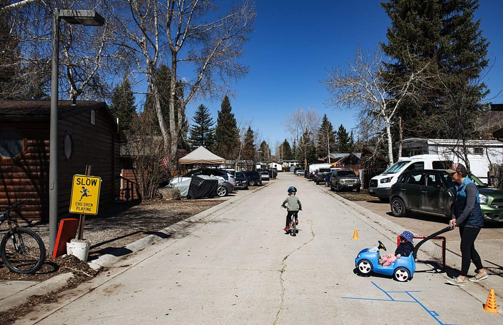 Cooper Gellert, 4, Sloane Gellert, 1, and Lacey Gellert take a stroll around their neighborhood in Aspen on Wednesday, April 8, 2020. (Kelsey Brunner/The Aspen Times)