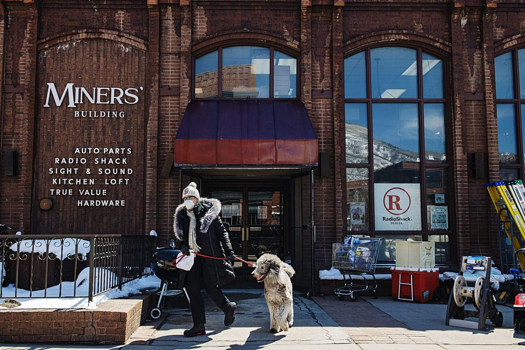 A woman and her dog leave the Miners' Building after making a purchase in Aspen on Friday, April 17, 2020.