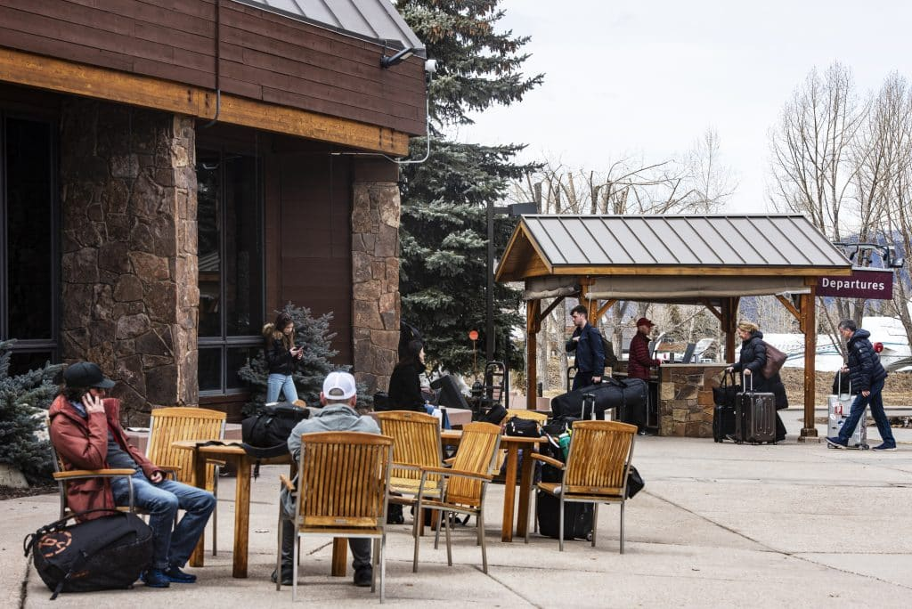 People wait outside of the departures entrance at the Aspen/Pitkin County Airport on Tuesday, March 17, 2020.