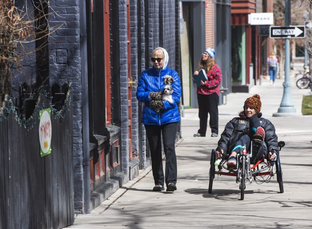 Cheryl Goldenberg, left, carries Evie as her and Leah Potts, right, take a stroll through downtown Aspen on Saturday, March 21, 2020. The two women are neighbors and friends.