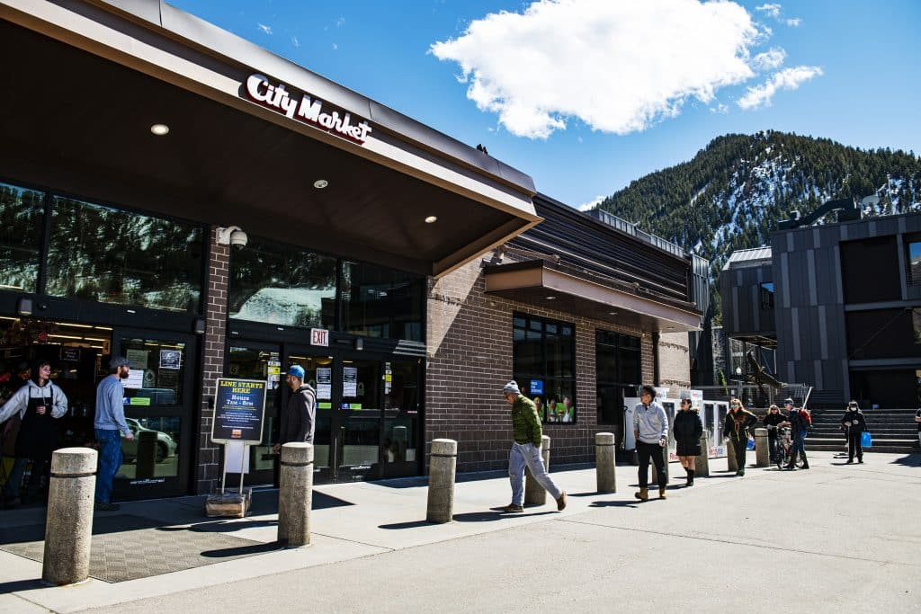 Five people begin to file inside Aspen's City Market after waiting in line at the door on Thursday, March 26, 2020. City Market is limiting the number of people allowed in the store at one time, as well as allowing senior citizens preferential treatment to enter the store first.