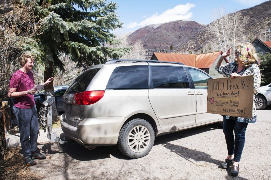 Challenge Aspen program director Deb Sullivan, right, holds a sign and says hello to Stefan Knight during a Wednesday drive-by at Knight's home on Wednesday, April 1, 2020. Even though Knight met them in the driveway, they made sure to abide by social distancing expectations.