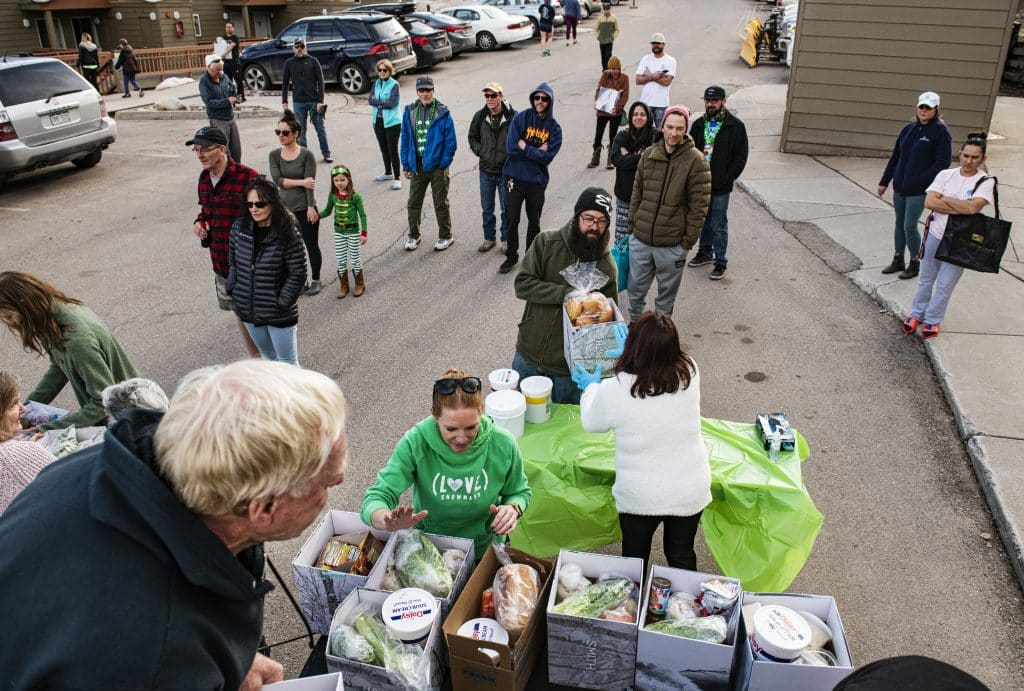 George Gordon, left, Whitney Gordon, center left, and other people from Gwyn's High Alpine hand out the restaurant's food supplies to Snowmass community members in the parking lot of the Housing Office on Tuesday, March 17, 2020. Gwyn's has officially closed its doors on Snowmass Mountain.