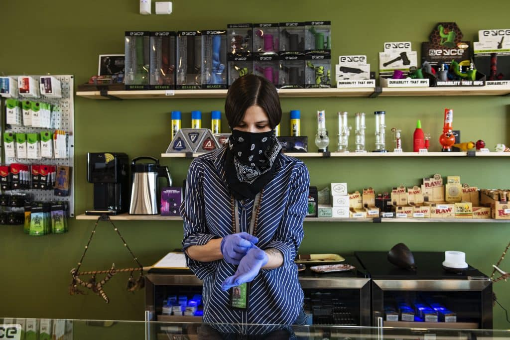 High Q store manager Leah Thomas puts on a bandana and gloves for health safety before opening at noon in Snowmass Village Mall on Tuesday, March 31, 2020.