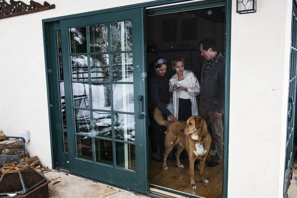 Dipika Peckham, left, Tara Peckham, 20, and Doug Peckham stand on the other side of their screen door with their dog Tycho while self-isolating due to potential coronavirus exposure on Thursday, March 19, 2020.