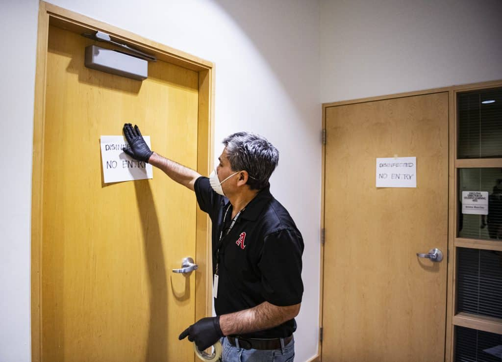 José Zavala hangs signs on the doors of rooms after the disinfecting crew have swept the area in Aspen High School on Thursday, March 19, 2020. They have been disinfecting the school all week and were working on the administrative offices in the high school.