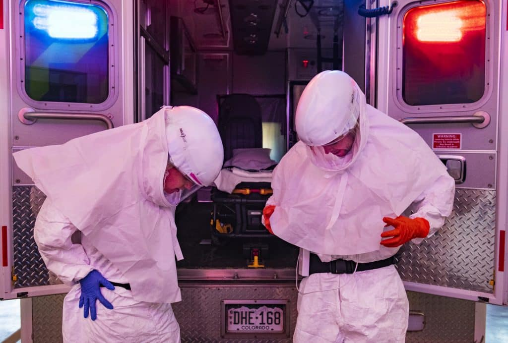 Aspen Ambulance District paramedic Lisa Hicks, left, and EMT Eric Tierney try on their powered air purifying respirator and Tyvek suit in the ambulance bay on Thursday, April 2, 2020. These particular PPE are used for transferring sick patients from Aspen Valley Hospital to a higher level of care facility, like Glenwood Springs or Denver.