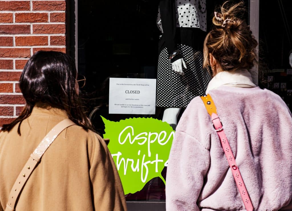 Two women look at the Aspen Thrift Shop's notice of closure due to the coronavirus on Thursday, March 12, 2020.