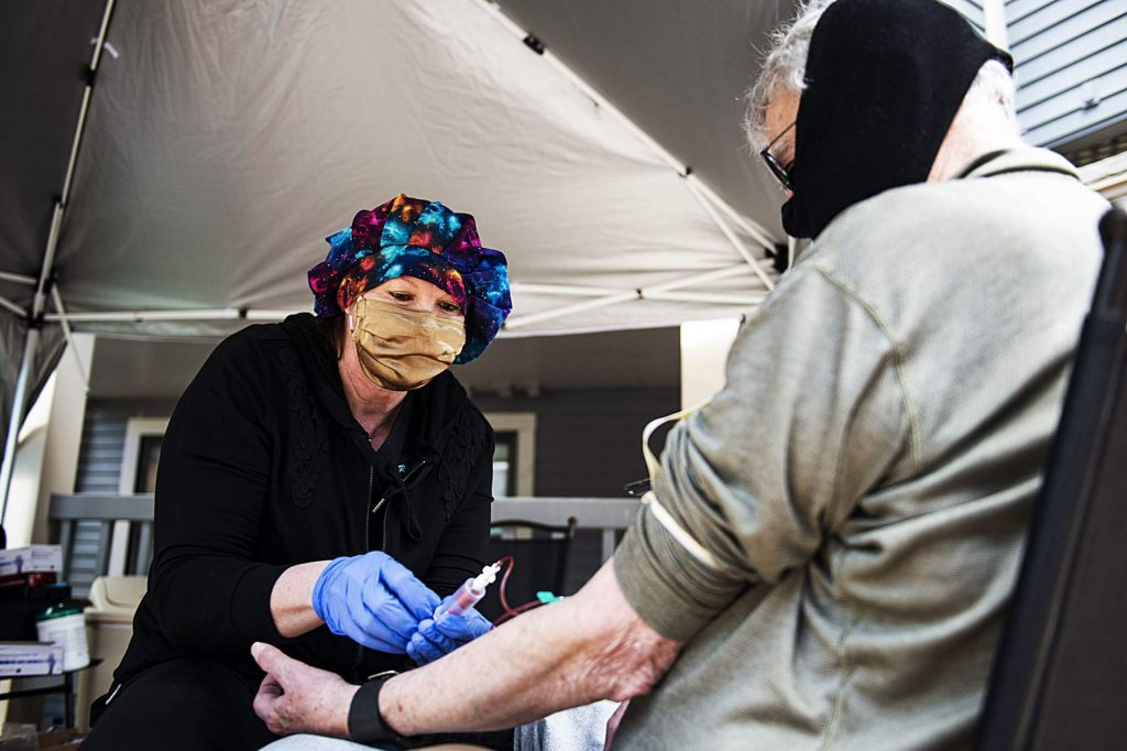 Dr. Gail King takes blood from Marshall Crouch in Aspen on Friday, April 10, 2020.