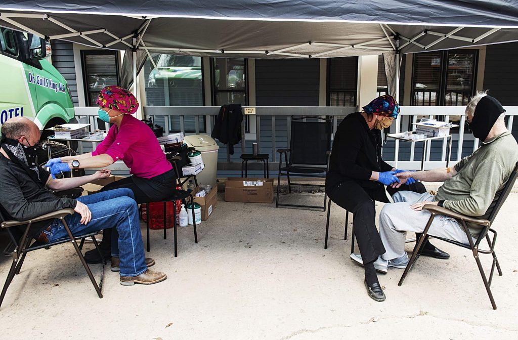 Registered Nurse Trudi Olson-Feast, center left, and Dr. Gail King, center right, draw blood from Steven Ferrell, left, and Marshall Crouch in Aspen on Friday, April 10, 2020.