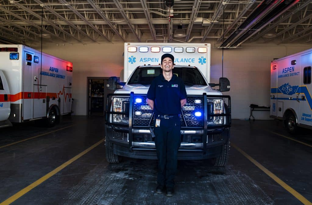 Aspen Ambulance District EMT Eric Tierney stands in the ambulance bay on Friday, April 3, 2020. Tierney is considered an essential worker in Colorado.