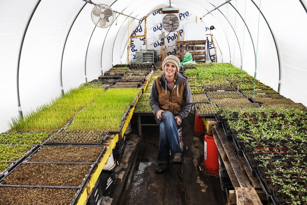 Two Roots Farm's Harper Kaufman sits in her greenhouse in Basalt on Thursday, April 2, 2020.