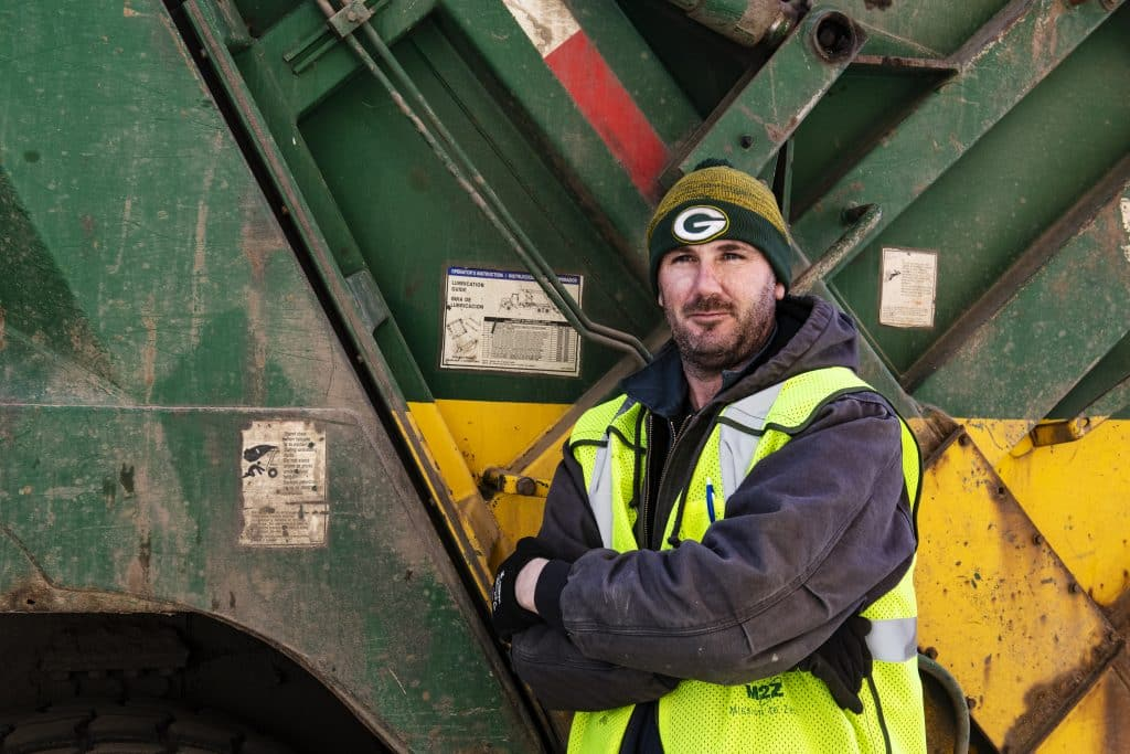 Waste Management driver assistant Thomas McCarten leans against a truck on Thursday, March 26, 2020. McCarten has worked for Waste Management for three and a half years and is considered an essential employee.
