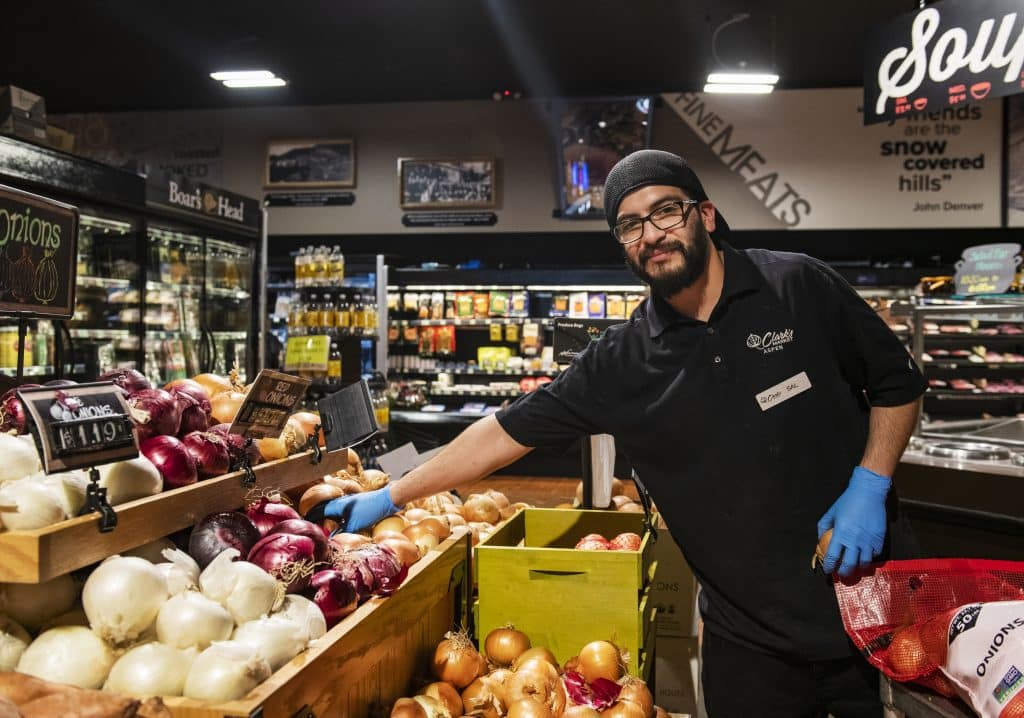 Clark's Market employee Sal Velasquez stocks onions on the floor in Aspen on Friday, April 3, 2020. Velasquez has worked at the store for four years. He said that since the crisis began in Aspen it had been really hard at the store trying to keep product on the shelves.