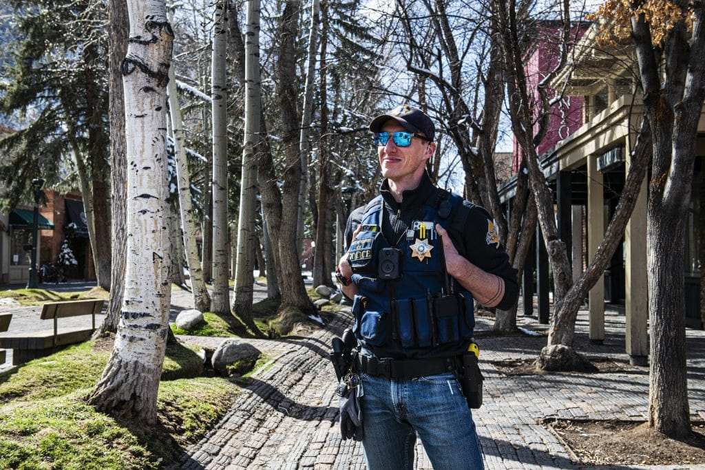 Aspen police officer Adriano Minniti stands on the walking mall on Friday, April 3, 2020.