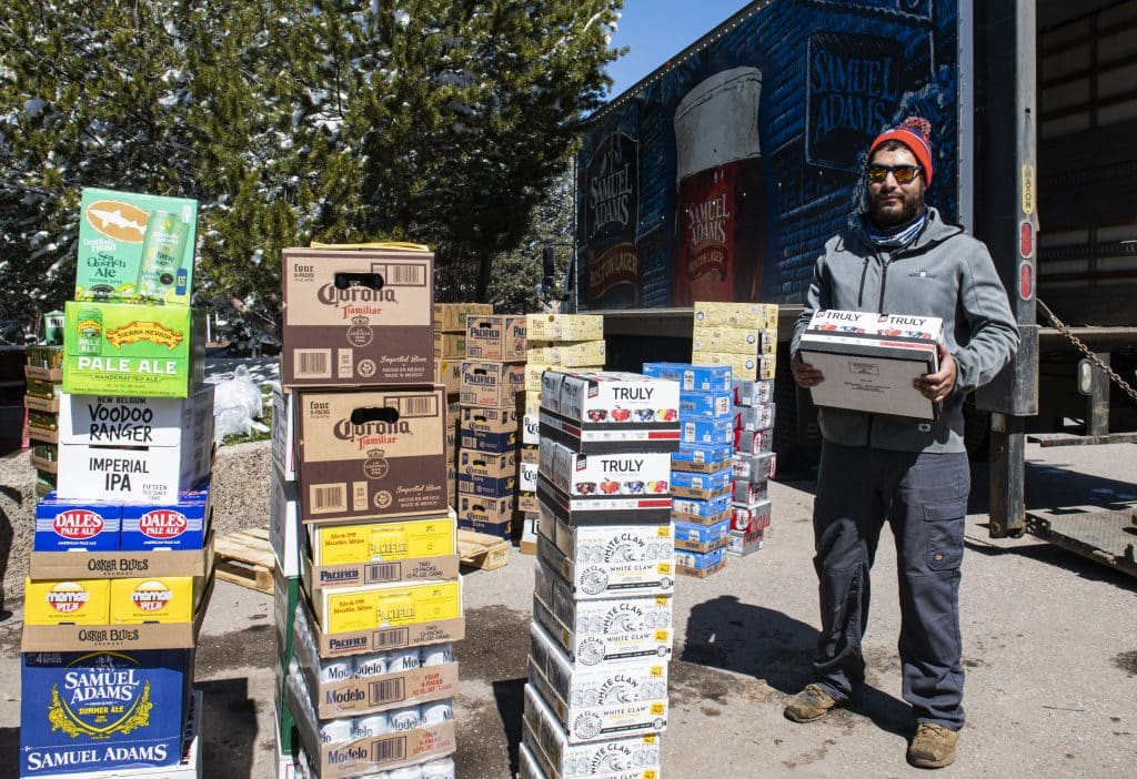 "Axel Chavez, a beer delivery driver, unloads a shipment of alcohol to Aspen on Thursday, April 2, 2020. ""We lost so much business with the bars and restaurants, so we're trying to keep on going as long as we can,"