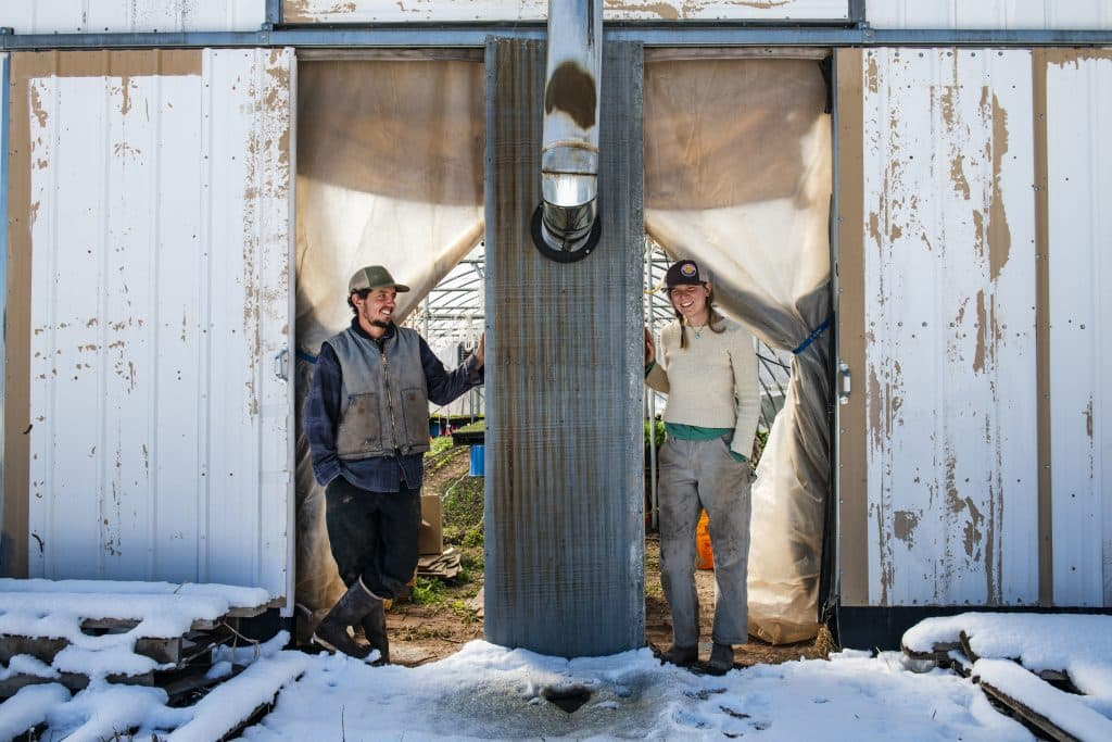 Wild Mountain Seeds farmers Casey Piscura, left, and partner Kirsten Keenan stand in the doorway of one of their greenhouses in Carbondale on Thursday, April 2, 2020. The two have had Wild Mountain Seeds for seven years and Piscura explained that every year they want to produce more food.