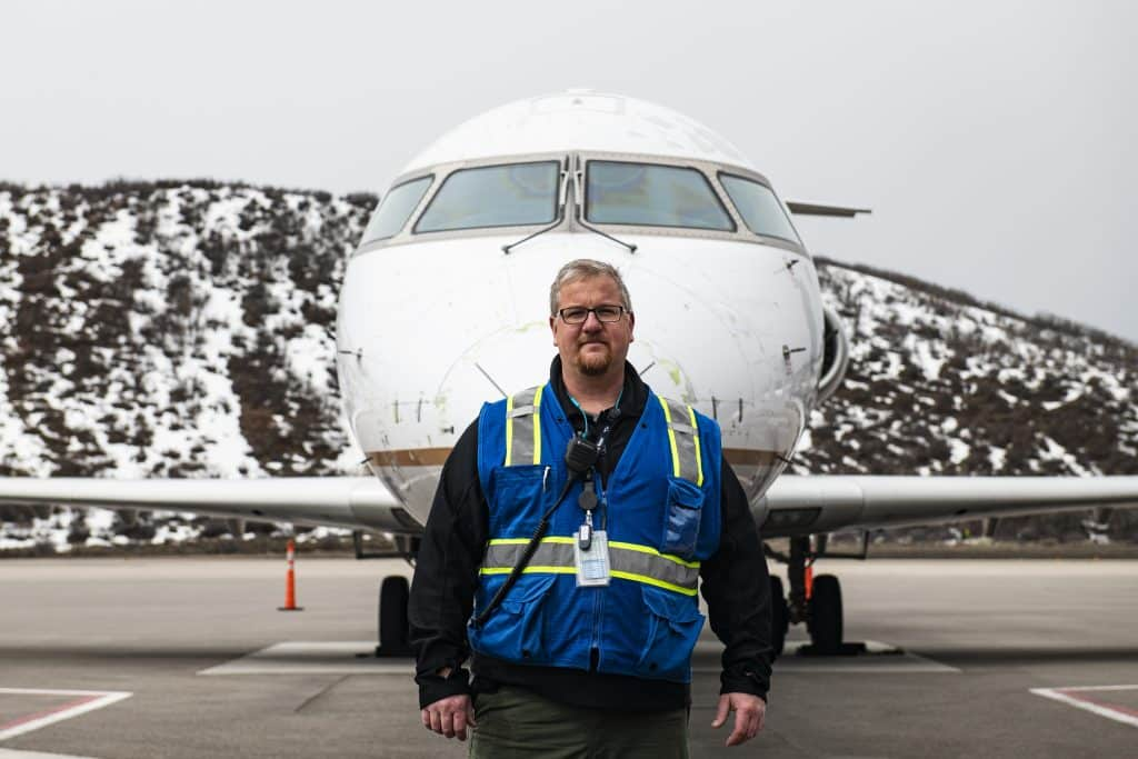 "Aspen/Pitkin County Airport senior operations security coordinator Adam Gardner stands on the ramp on Thursday, April 2, 2020. Gardner has been with the Aspen Airport for three years. He went to University of North Dakota and graduated right before 9/11. ""Everybody who is an essential worker, we're all doing our best to limit our exposure and go a step further to ensure the safety of our passengers,"" said Gardner."