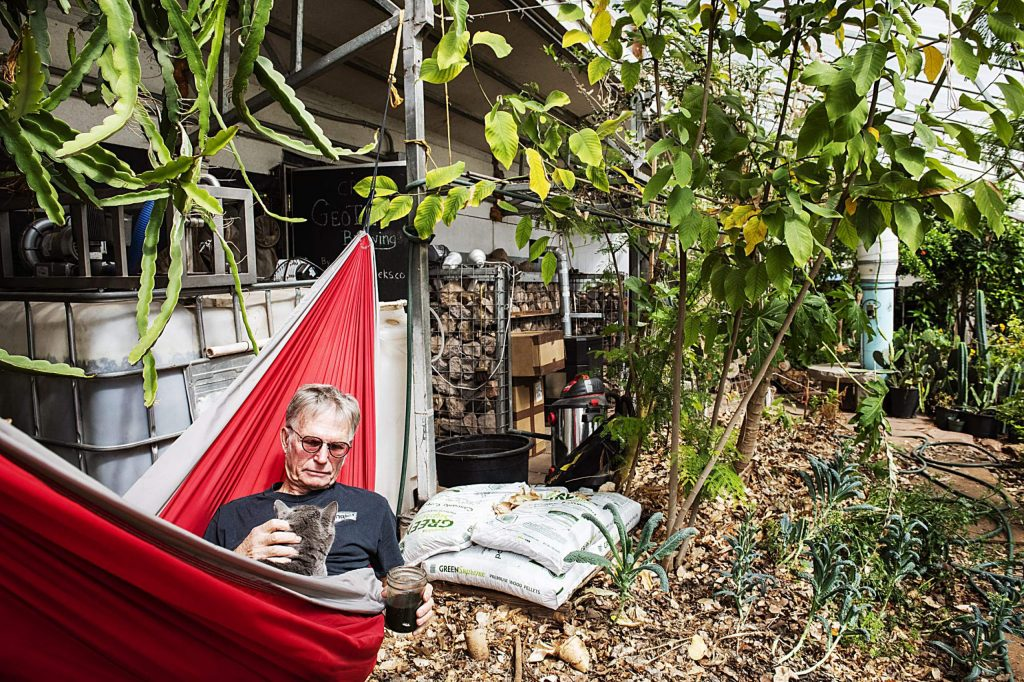 Jerome Osentowski, 78, holds one of his two cats in his hammock while enjoying his daily smoothie in a greenhouse at Central Rocky Mountain Permaculture Institute in Basalt on Wednesday, April 1, 2020. (Kelsey Brunner/The Aspen Times)