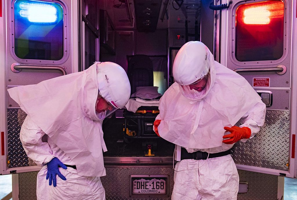 Aspen Ambulance District paramedic Lisa Hicks, left, and EMT Eric Tierney try on their powered air purifying respirator and Tyvek suit in the ambulance bay on Thursday, April 2, 2020. These particular PPE are used for transferring sick patients from Aspen Valley Hospital to a higher level of care facility, like Glenwood Springs or Denver. (Kelsey Brunner/The Aspen Times)