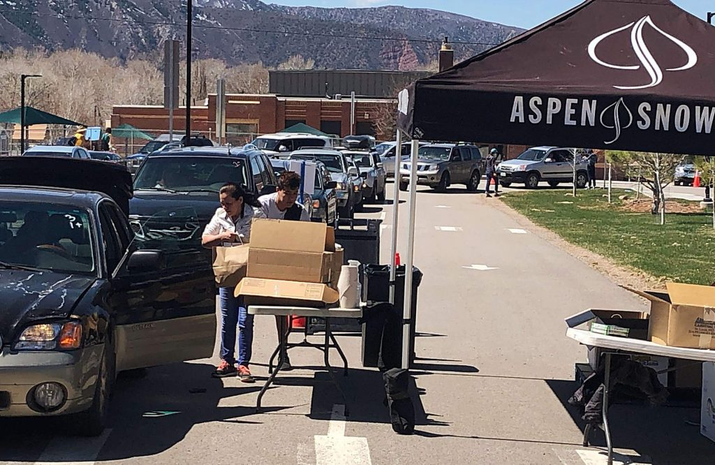 A couple load food into their car Thursday as a long line of vehicles waits their turn at Basalt Middle School. Aspen Skiing Co. employees volunteered to distribute food provided by Food Bank of the Rockies.
