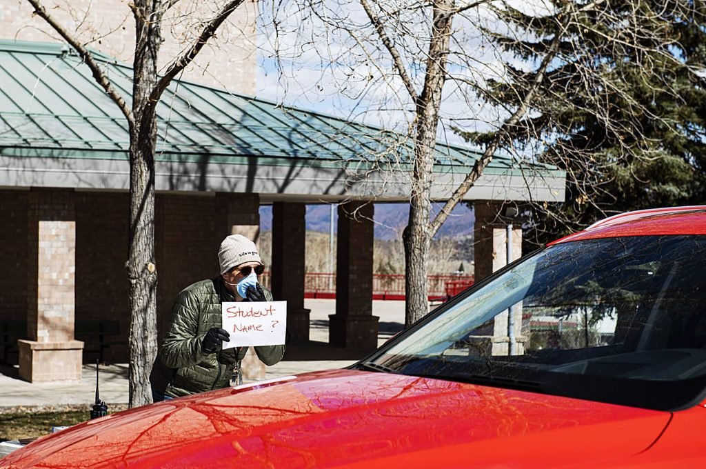 Aspen Elementary School principal Chris Basten holds a sign up to a parent's window outside of the school on Wednesday, April 1, 2020.