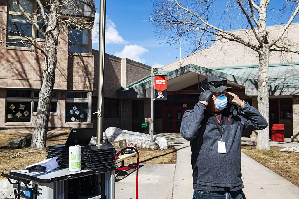 Aspen Elementary School technology integrator Dave Fuentes puts his mask on while preparing and distributing student's laptops outside of the school on Wednesday, April 1, 2020.