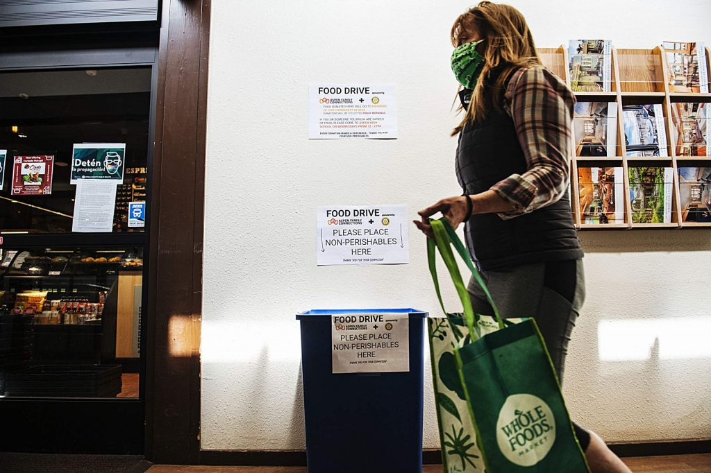A woman walks past a non-perishable food drive bin outside of Clark's Market in Snowmass on Tuesday, April 21, 2020. The food drive bin is gathering non-perishables for Aspen Family Connections. (Kelsey Brunner/The Aspen Times)