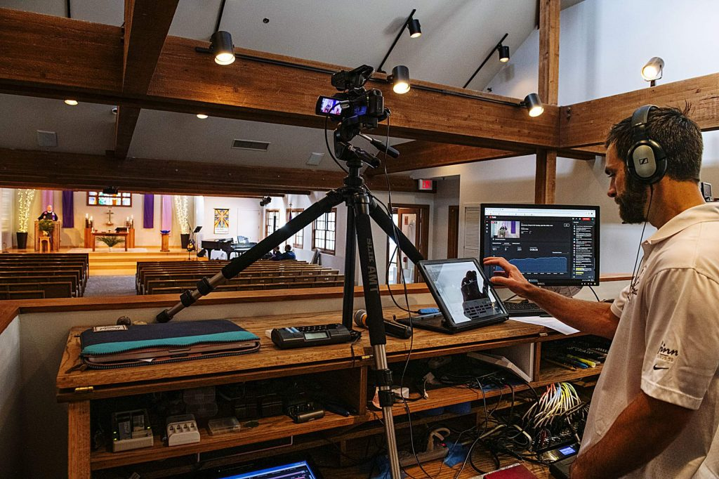 Adam Gilbert manages the recording of the Snowmass Chapel service while Senior Pastor Robert de Wetter gives a Palm Sunday service on Sunday, April 5, 2020.