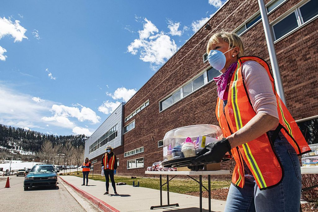 Volunteer Arabella Beavers carries a tray of cupcakes to a waiting car during the Aspen Family Connections food drive at the middle school on Wednesday, April 1, 2020. The line of cars wrapped around to the high school to receive food. (Kelsey Brunner/The Aspen Times)