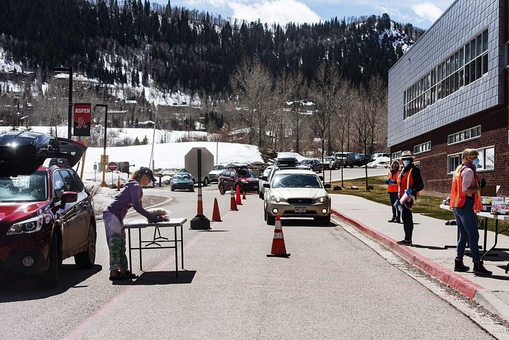 A community member picks up items left on the table for her by Aspen Family Connections volunteers at the community food drive on Wednesday, April 1, 2020. (Kelsey Brunner/The Aspen Times)