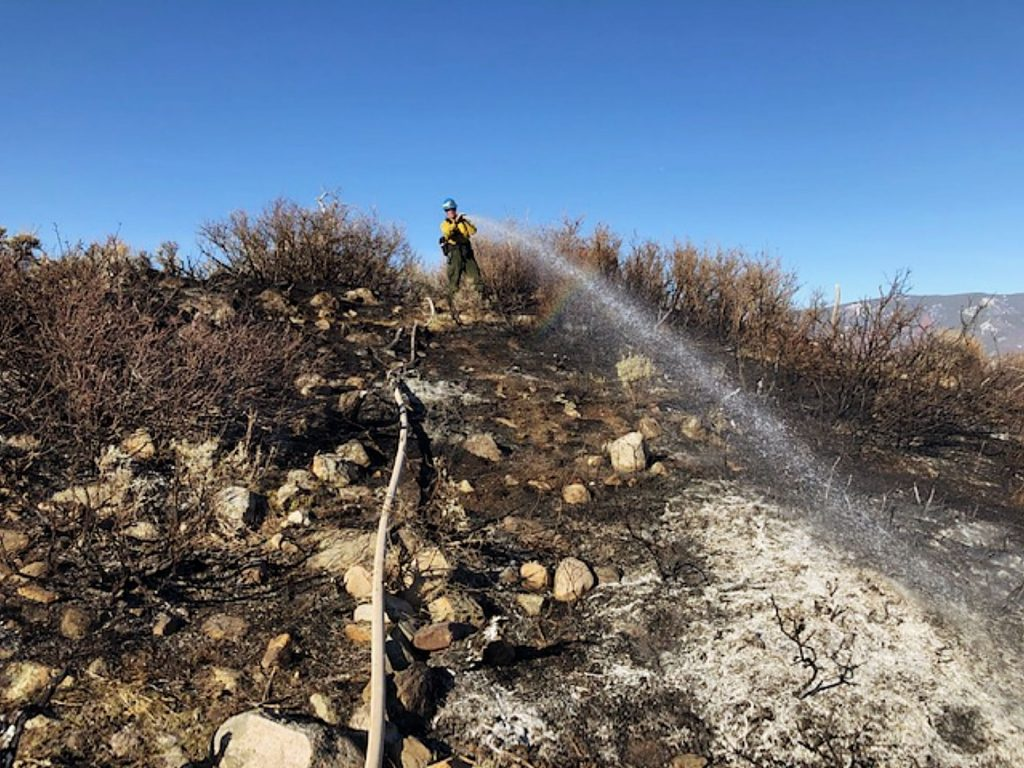 A firefighter with Roaring Fork Fire Rescue doses a hotspot in a wildland fire off of Snowmass Creek Road on Wednesday.