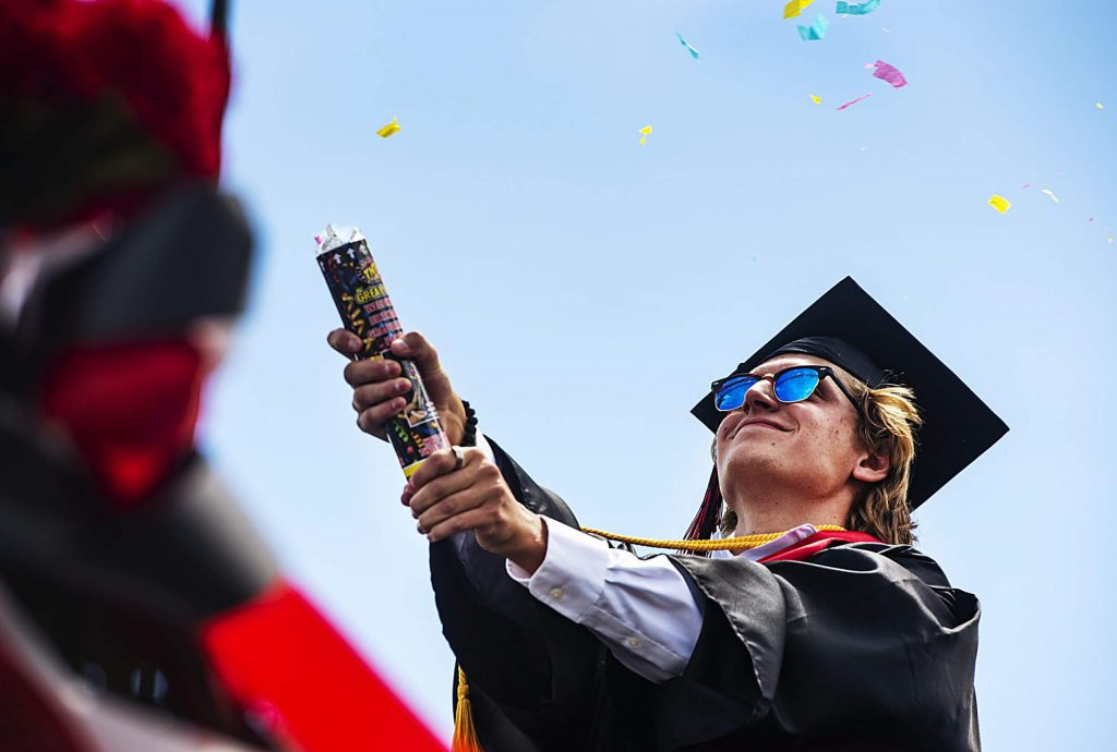 Richie Simeone pops confetti after crossing the stage during Aspen High School's graduation at Buttermilk on Saturday, May 30, 2020. (Kelsey Brunner/The Aspen Times)
