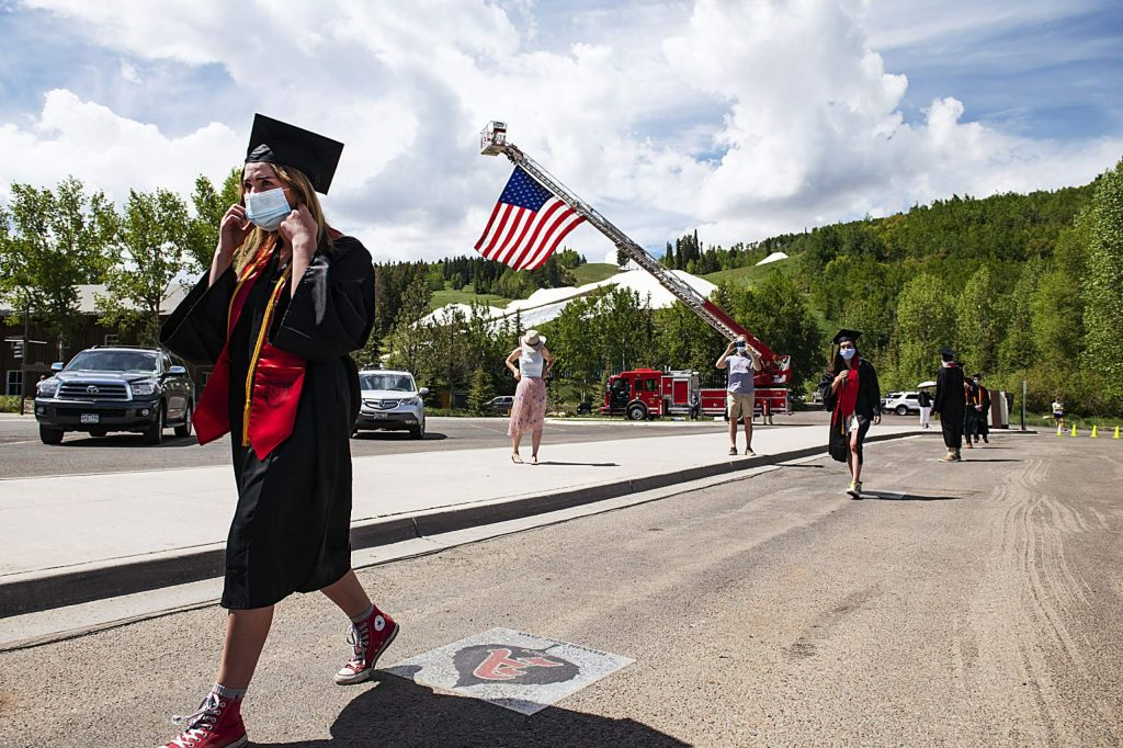 A graduate prepares to take her mask off as she approaches the stage during Aspen High School's graduation ceremony at Buttermilk on Saturday, May 30, 2020. (Kelsey Brunner/The Aspen Times)