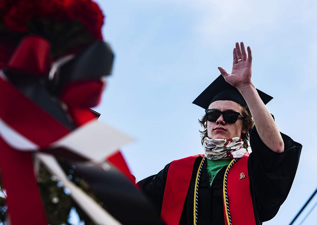 Graduate Jack Seamans waves at family as he crosses the stage during Aspen High School's graduation at Buttermilk on Saturday, May 30, 2020. (Kelsey Brunner/The Aspen Times)