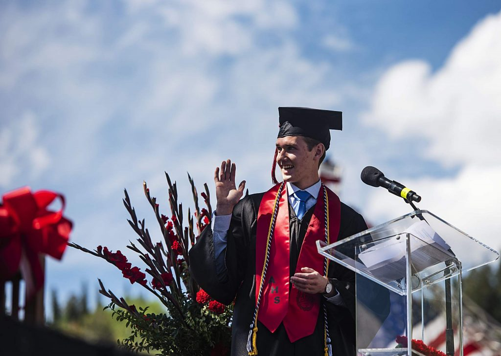Riley Johnson waves to the commencement speaker, Chris Davenport, after introducing him during Aspen High School's graduation at Buttermilk on Saturday, May 30, 2020. (Kelsey Brunner/The Aspen Times)